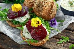 土气整粒小圆面包用酸奶干酪、火箭叶子、甜菜根切片和可食的中提琴花 素食食物 免版税库存图片