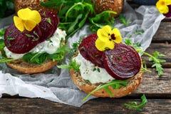 土气整粒小圆面包用酸奶干酪、火箭叶子、甜菜根切片和可食的中提琴花 素食食物 库存照片