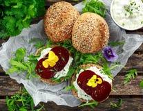 土气整粒小圆面包用酸奶干酪、火箭叶子、甜菜根切片和可食的中提琴花 素食食物 库存图片