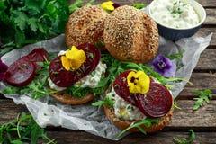 土气整粒小圆面包用酸奶干酪、火箭叶子、甜菜根切片和可食的中提琴花 素食食物 图库摄影