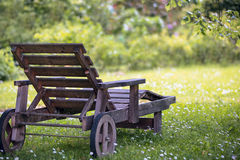 土气木可躺式椅在国家庭院里 免版税图库摄影