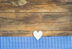 土气木心脏和蓝色方格的织品在棕色板条 免版税库存照片