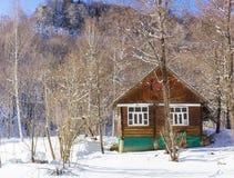 土气木房子在山的一个多雪的冬天森林里 库存照片