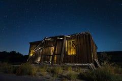 土气木棚子在晚上在沙漠 免版税库存图片