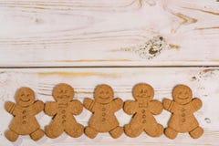 土气木背景的圣诞节微笑的姜饼人 库存照片
