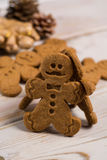 土气木背景的圣诞节微笑的姜饼人 库存图片