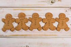 土气木背景的圣诞节微笑的姜饼人 免版税库存图片