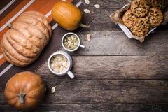 土气样式南瓜、种子和曲奇饼与坚果在桌上 免版税库存照片