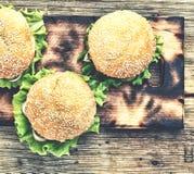 土气样式,顶视图 在一张木桌上的汉堡包 土气 免版税库存照片