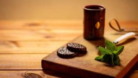 土气桌用有些巧克力和薄荷叶在一杯咖啡旁边 图库摄影