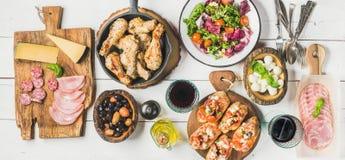 土气桌设置了与鸡、沙拉、不同的快餐和酒 免版税库存图片