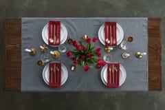 土气桌设置顶视图与红色郁金香花束、失去光泽的利器、酒杯、蜡烛和空的板材的在桌面 库存照片