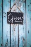 土气海滩前的商店开放标志 免版税图库摄影