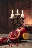 土气的生活仍然称呼 果子石榴,柠檬,说谎在与一杯的一张木桌上酒和蜡烛在壁炉 免版税库存图片