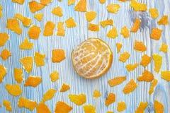 土气的背景 异乎寻常的果子 蜜桔一张顶上的照片没有果皮的 在木蓝色桌上的被剥皮的水多的蜜桔和 库存照片