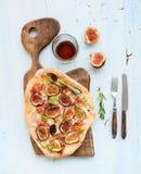 土气自创薄饼用在黑暗的木服务的无花果、熏火腿和无盐干酪乳酪上在浅兰的背景 库存照片