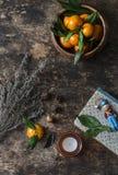 土气静物画用新鲜的普通话、干草本、书、蜡烛和一个自由空间文本的在木背景,顶视图 库存图片
