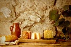 土气静物画、乳酪品种、面包和酒 免版税库存图片