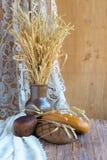 土气静物画用面包,麦子的耳朵在木背景的 免版税库存照片