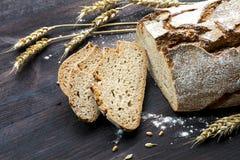 土气面包和切片用麦子在黑暗的木头 库存图片