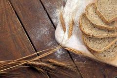 土气面包和麦子在一张老葡萄酒木头桌上 库存图片