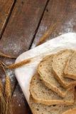 土气面包和麦子在一张老葡萄酒木头桌上 免版税库存照片