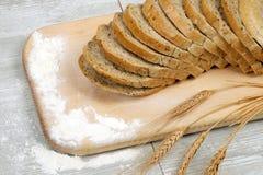 土气面包和麦子在一张老葡萄酒灰色木桌上 免版税图库摄影