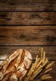 土气面包和麦子在葡萄酒木头桌上 免版税库存图片