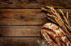 土气面包和麦子在葡萄酒木头桌上 库存照片