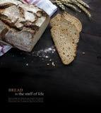 土气面包大面包和切片在退色对黑色, sampl的黑暗的木头 免版税图库摄影