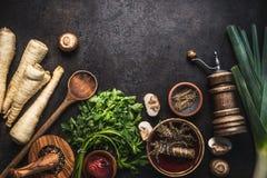 土气食物背景用荷兰芹在黑暗的土气桌上的根菜类、草本、香料、韭葱和蘑菇蘑菇与厨房 库存照片