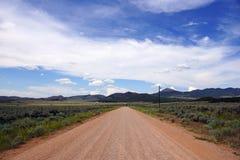 土沙漠路和蓝色多云天空 免版税图库摄影