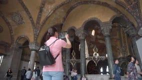 土耳其、伊斯坦布尔,Ayasofya,2019年,一个游人有一个背包的在他的后和一种片剂在他的拍照片的手上 股票视频