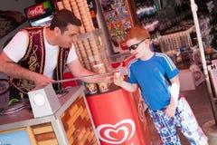 土耳其人给传统土耳其冰淇凌一个小男孩o 库存图片