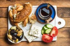 土耳其传统早餐用希腊白软干酪、菜、橄榄、simit百吉卷和红茶在白陶瓷委员会 库存照片