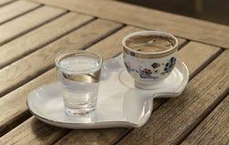 土耳其咖啡和水在一个简单的盛肉盘 免版税图库摄影