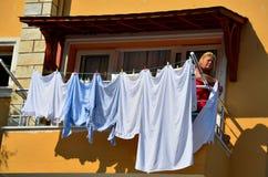 土耳其妇女垂悬洗衣店从阳台烘干 库存图片