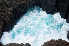 土耳其玉色水洞与飞溅风大浪急的海面的坑孔 免版税图库摄影