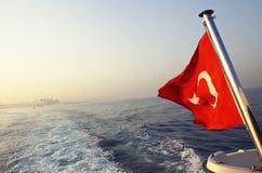 土耳其的旗子一条小船的在Bosphorus海峡 库存照片