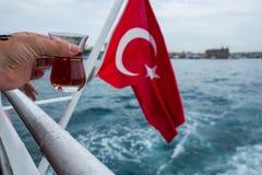 土耳其茶和旗子在一条小船在伊斯坦布尔,土耳其 免版税库存图片