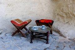 土耳其街道咖啡馆在Goreme露天博物馆 木传统桌和椅子在街道上 两个杯子土耳其咖啡 免版税库存照片