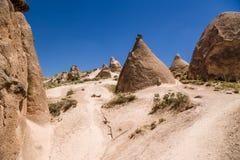 土耳其,卡帕多细亚 与风化柱子的美好的山风景在谷Devrent的 免版税库存照片