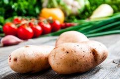 土豆和菜在桌上 免版税库存图片