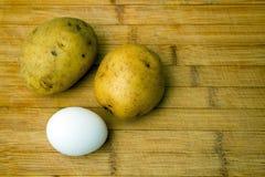 土豆和鸡蛋在木桌-成份上-顶面焦点 免版税库存图片