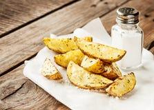 土豆在土气木桌上楔住-禁止菜单 库存照片