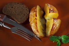土豆在桌上的黏土板材烘烤了 图库摄影