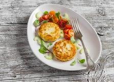 土豆小馅饼和新鲜的蕃茄和芹菜沙拉在一块轻的陶瓷板材 免版税库存图片