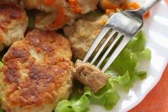 土豆小馅饼和炖煮的食物在一块白色板材 免版税库存照片