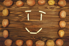 土豆微笑框架在木纹理的 库存照片