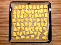 土豆未加工在烘烤的盘子的烘烤的纸 免版税图库摄影